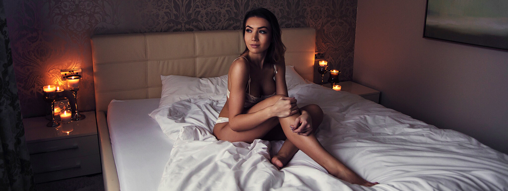 Woman wearing lingerie in bedroom with dimmed lights & candles