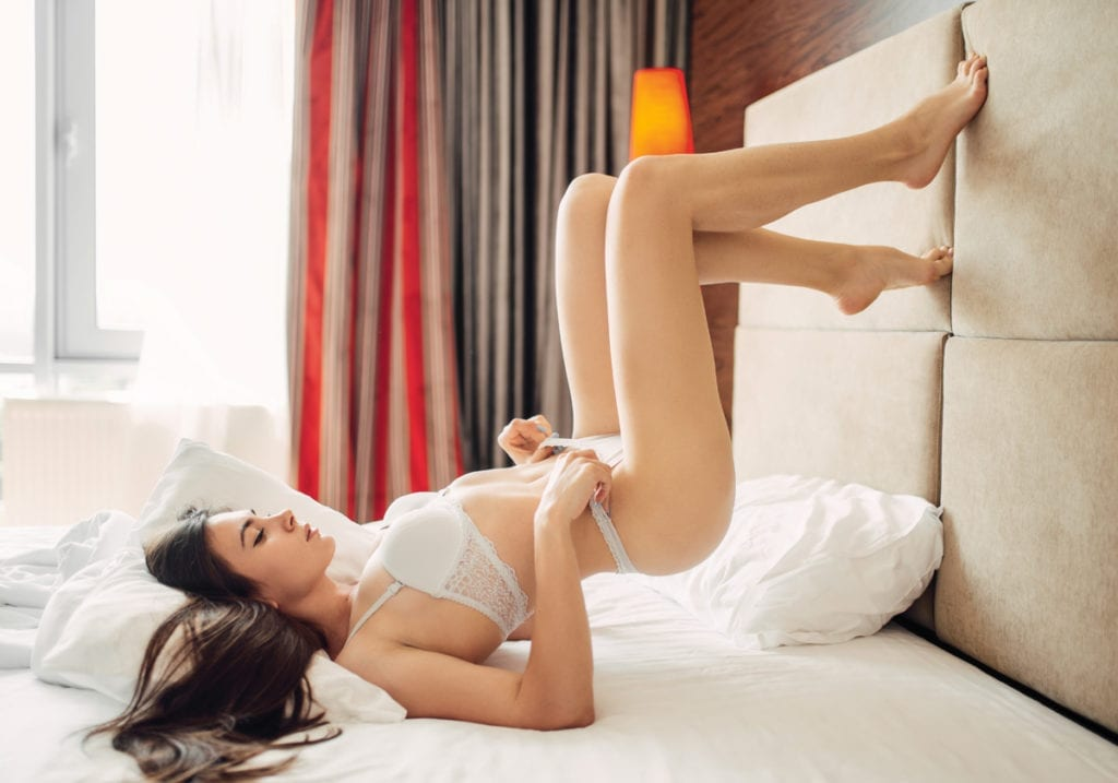 Woman in white lingerie in hotel room