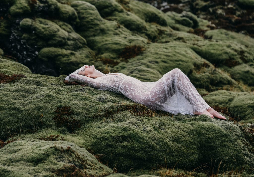 Woman laying on mossy rocks in elegant lingerie