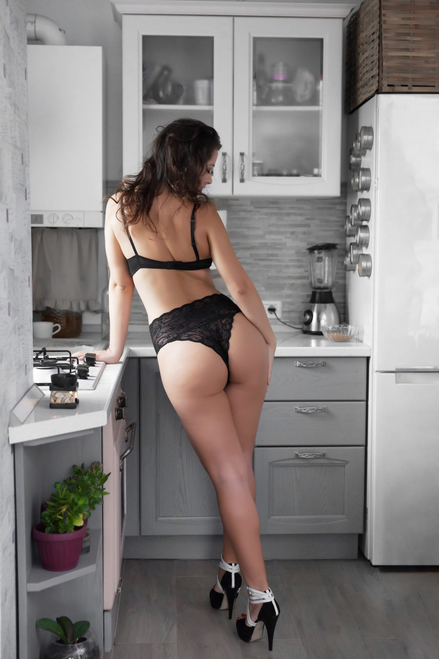 Sensual women touching hers booty softly in the kitchen.